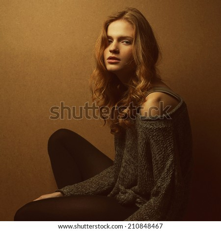 Emotive portrait of fashionable model with long curly red hair and natural make-up posing over wooden background. Perfect skin. Urban grunge style. Studio shot