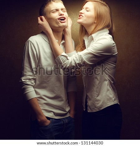 Emotive portrait of gorgeous red-haired (ginger) fashion twins in white shirts playing and laughing over golden background together. Sister pulling brother's ears. Studio shot.