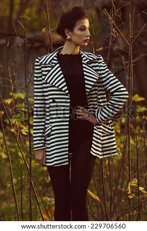 Emotive portrait of Hollywood diva, film star walking in the park. Evening time. Sunny spring weather. Young woman in luxurious trendy striped jacket. Golden earrings. Outdoor shot  - stock photo
