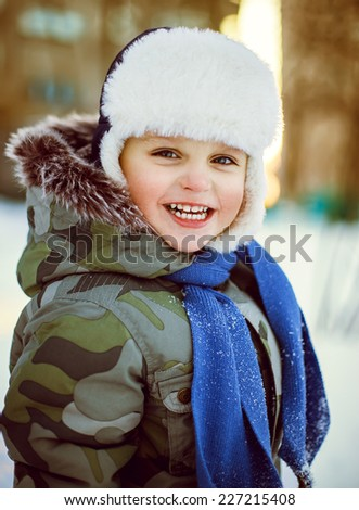 Emotive portrait of little smiling boy in winter clothes.  - stock photo