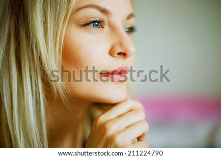 Emotive portrait of young beautiful woman with long blond hair. Close up - stock photo