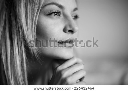 Emotive portrait of young beautiful woman with long blonde hair. Close up