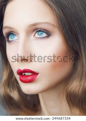 Emotive portrait of young beautiful woman with perfect make up. Red lips and blue eyes. - stock photo