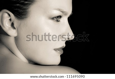 Emotive portrait of young woman with naked shoulder on black background