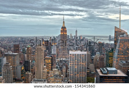 Empire State and Manhattan buildings with lights on  from a high view, in the dusk of New York City, USA. - stock photo