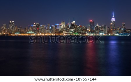 Empire State Building and Midtown Manhattan skyline at night as seen from Hoboken, New Jersey - stock photo