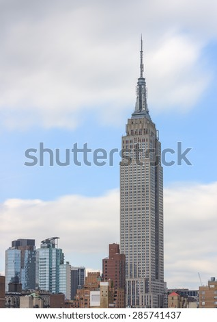 Empire state building by day, white clouds and blue sky in the background - June 3, 2015, Manhattan, New York City, NY, USA