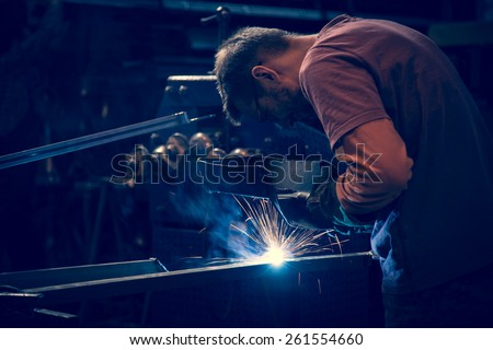 Employee at the factory welding steel tubes using MIG MAG welder. - stock photo