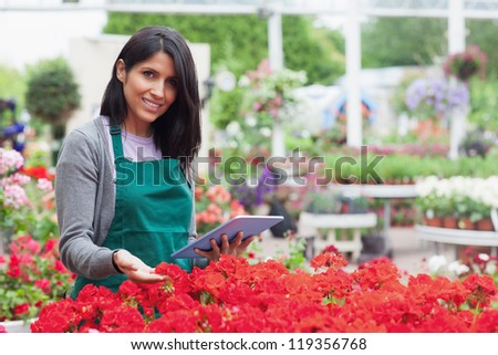 Employee choosing flowers in garden center with tablet pc - stock photo