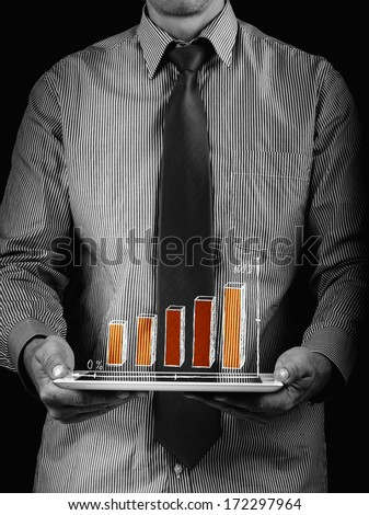 employee financial holding the tablet in hands and shows a graph - stock photo