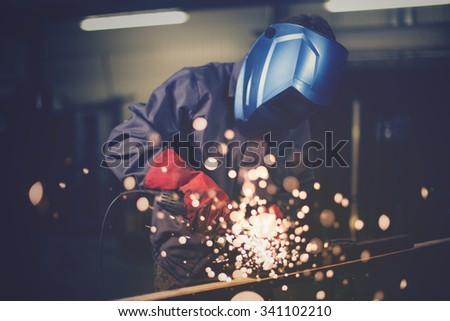 Employee grinding steel with sparks - focus on grinder. - stock photo