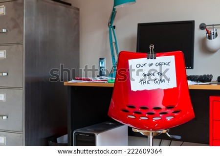 Employee leaves note on back of office chair: Out of Office. Gone to The Gym! - stock photo
