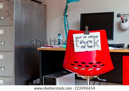 Employee leaves note on back of office chair: Out of Office. Gone to The Spa! - stock photo