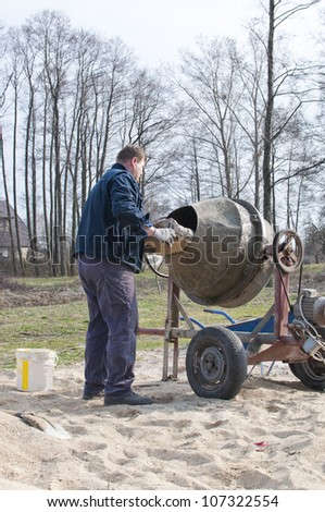 employee loads the sand into the mixer - stock photo