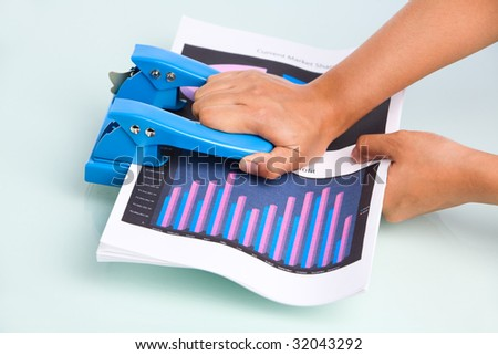 Employee's hand is pressing hole puncher where the documents placed in. Taken from side view. - stock photo