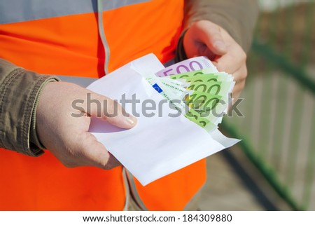 Employee's hands with euro banknotes in envelope - stock photo
