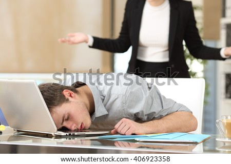 Employee sleeping with the face over the laptop with his angry boss watching back at office - stock photo