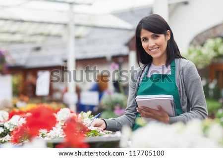 Employee taking notes in the garden centre while smiling - stock photo