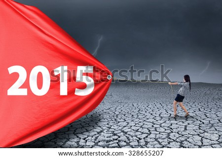 Employee try to pull a big banner with number 2015 on drought land, symbolizing a change