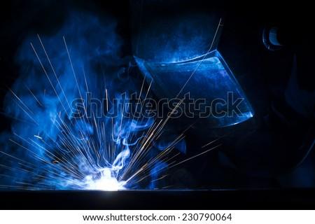 Employee welding using MIG/MAG welder. - stock photo