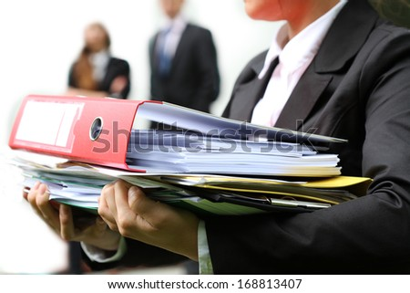 Employee with heap of documents and papers