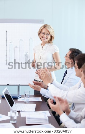 Employees applauding a woman in office - stock photo