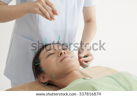 Employees hit the acupuncture to woman's face at the salon - stock photo