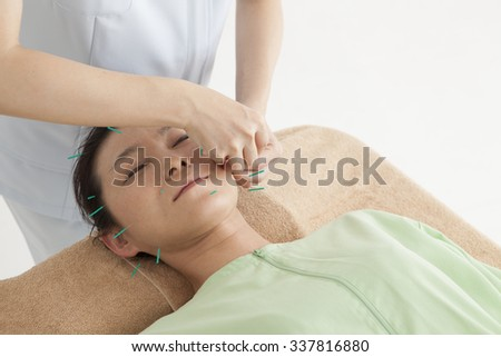 Employees hit the acupuncture to woman's face in the clinic - stock photo