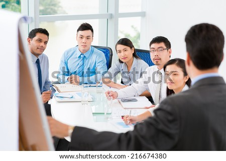 Employees listening to the chief at the briefing - stock photo