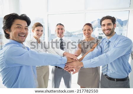 Employees putting hands together in a tower - stock photo