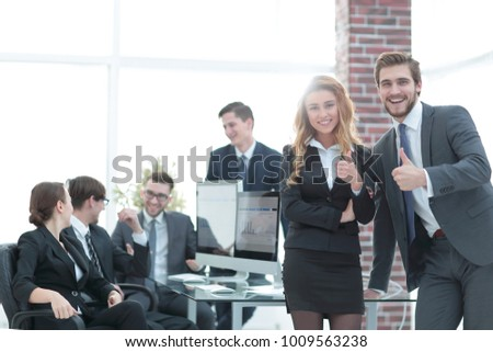 employees showing thumbs up in office.