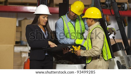 Employees work together in shipping warehouse - stock photo
