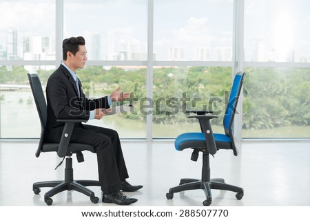 Employer interviewing an empty office chair, side view - stock photo