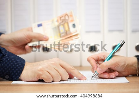 employer or businessman showing where to sign  in exchange to give money or severance - stock photo