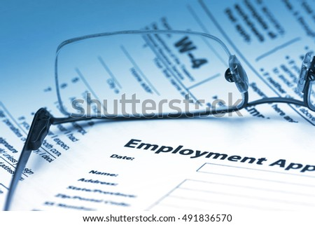 Employment agreement with W-4 form through reading glasses.