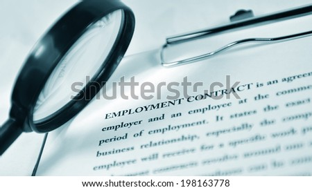 Employment contract under the magnifying glass - stock photo
