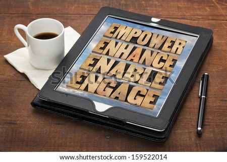 empower, enhance, enable and engage - motivational business concept - a collage of words in letterpress wood type on a digital tablet - stock photo
