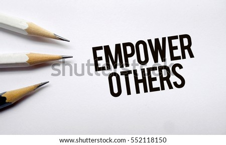 Empower others memo written on a white background with pencils