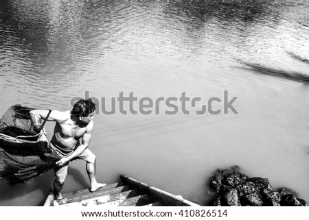 Empower,Samutsongkram,Thailand.14 April 2016,fisherman trow black net for fishing shrimp and fish on pond in black and white