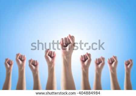 Empowering women power, human rights and labor day concept with strong fist hands isolated on blue sky