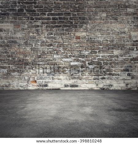 Empty abstract interior background with dark old brick wall and asphalt floor - stock photo