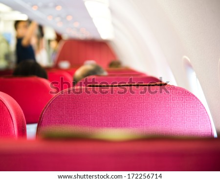 empty airplane interior with  red seats and window. - stock photo