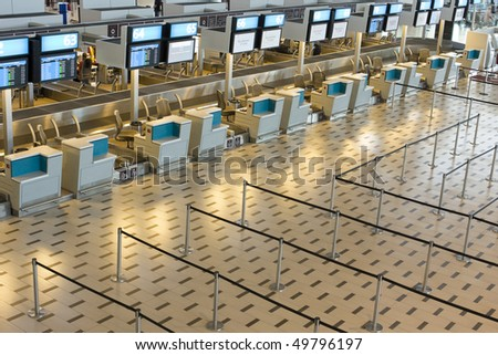 Empty airport terminal check-in desks - stock photo