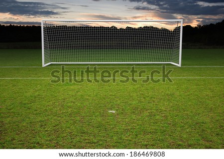 empty amateur football goal posts and nets shot at sunset - stock photo