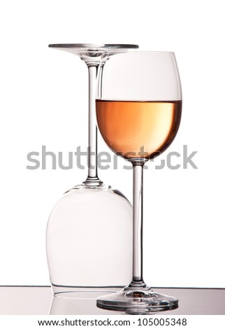 Empty and full crystal wine glasses against white background - stock photo