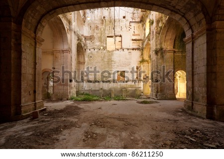 Empty and old church hall covered by nature - stock photo