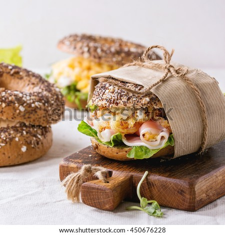 Empty and staff sprinkle seeds Whole Grain bagels with scrambled eggs, pea sprout, fried onions and prosciutto ham, making on white linen tablecloth and small wooden chopping board. Square image
