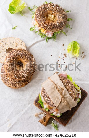 Empty and staff Whole Grain bagels with scrambled eggs, pea sprout, fried onions and prosciutto ham, making on white linen tablecloth and small wooden chopping board. Flat lay - stock photo