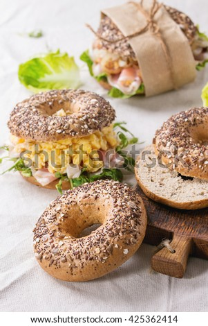 Empty and staff Whole Grain bagels with scrambled eggs, pea sprout, fried onions and prosciutto ham, making on white linen tablecloth and small wooden chopping board. - stock photo