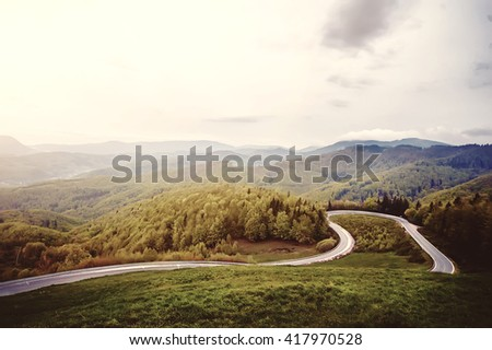 empty asfalt road trought the deep forest on sunrise. natural background. vintage picture - stock photo